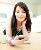 Dreamy woman listening music lying on the floor — Stock Photo