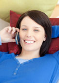 Jolly teen girl talking on phone lying on a sofa — Stock Photo