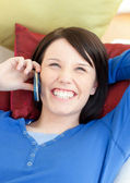 Laughing young woman talking on phone lying on a sofa — Stock Photo