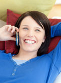 Happy young woman talking on phone lying on a sofa — Stockfoto