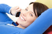 Joyful young woman talking on phone lying on a sofa — Stock Photo