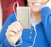Close-up of a young woman listening music lying on a sofa — Stock Photo