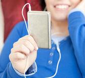 Close-up van een jonge vrouw luisteren muziek liggen op een sofa — Stockfoto