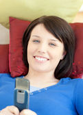 Smiling teen girl sending a text lying on a sofa — Stock Photo