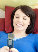Pretty teen girl sending a text lying on a sofa — Stock Photo