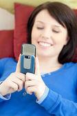Cheerful teen girl sending a text lying on a sofa — Stock Photo