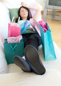 Exhausted woman relaxing after shopping — Stock Photo