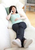 Charming woman talking on phone lying on a sofa — Stock Photo
