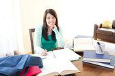 Niña adolescente sonriente estudiando — Foto de Stock