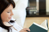 Serious woman reading a book lying on a sofa — Stock Photo