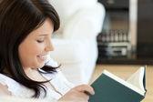 Atraktivní žena čte knihu ležící na pohovce — Stock fotografie
