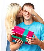 Vrouw geven een geschenk en een kus een man — Foto de Stock