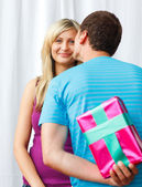 Man giving a present to a woman and a kiss — Stock Photo