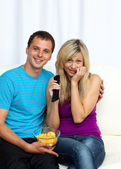 Couple watching a film on television and eating crisps — Stock Photo