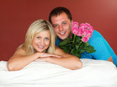 Couple on sofa holding a rose bouquet — Stock Photo