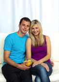Couple watching television and eating crisps — Stock Photo