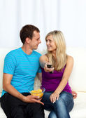 Lovers watching television and eating crisps — Stock Photo