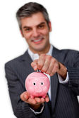 Businessman saving money in a piggybank — Stock Photo