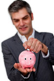 Sophisticated male executive saving money in a piggybank — Stock Photo