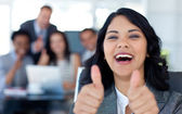 Happy businesswoman with thumbs up in office — Stock Photo