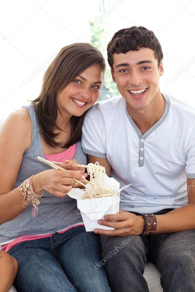 Sorridente coppia di adolescenti mangiare pasta foto - Coppia di amatori che scopano sul divano ...