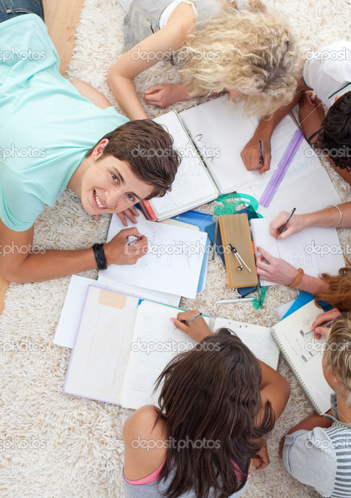 Group of Teenagers lying on the ground studying together — Stock Photo #10278318
