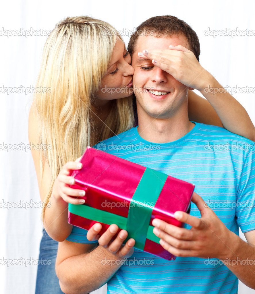 Woman giving a present and a kiss to a man covering his eyes — Stock Photo #10279511