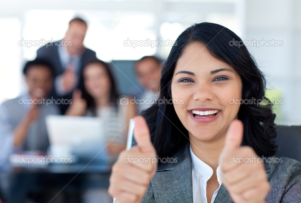 Portrait of a businesswoman with thumbs up in office with her team in the background  Stock Photo #10279669