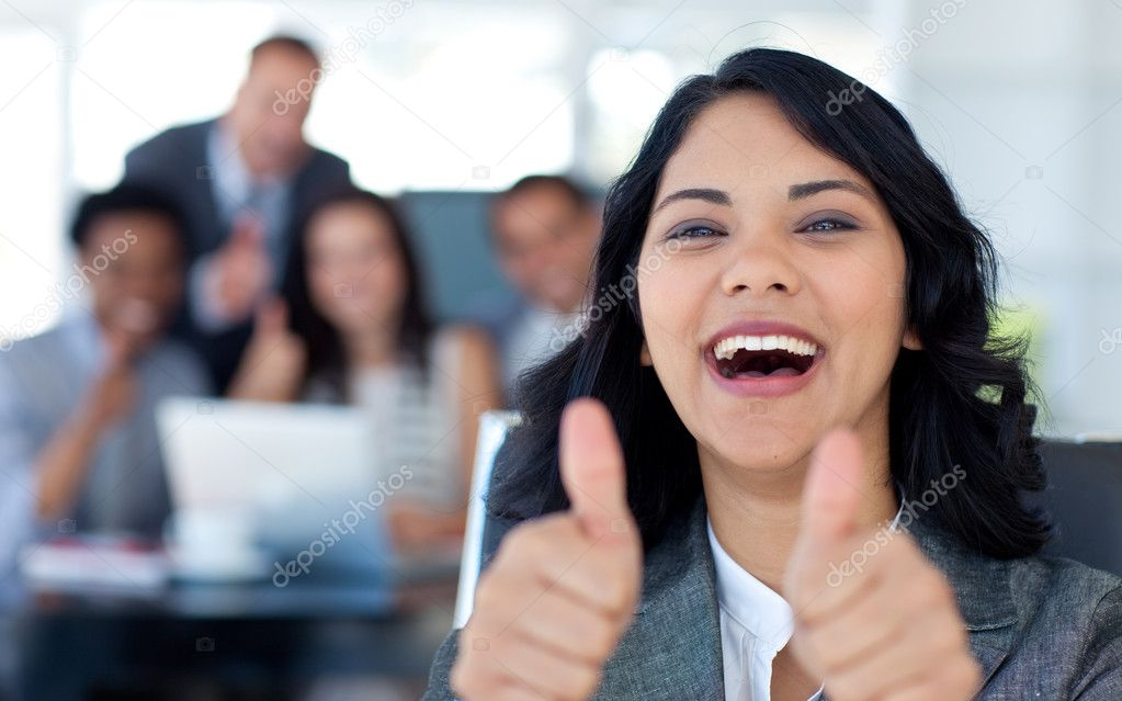 Happy businesswoman with thumbs up in office with her team in the background — Stock Photo #10279673