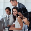 Stock Photo: Businesswoman in a call center with her team and manager