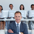 Friendly manager in call center with his team in the background — Stock Photo