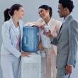 Business speaking next to a water cooler — Stock Photo