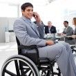 Businessman in a wheelchair on phone during a meeting — Stock Photo #10280564