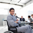 Foto Stock: Attractive businessman sitting in a wheelchair with folded arms
