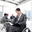Portrait of a smiling businesswoman in a wheechair - Stock Photo