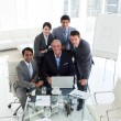 Senior businessman working with his team at a computer - Stock Photo