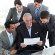 Stock Photo: Senior manager showing a document to his team