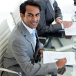 Confident businessman sitting at a conference table - Stock Photo
