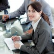 Stock Photo: Smiling businesswomstudying document in meeting