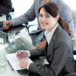 Smiling businesswoman studying a document in a meeting — Stock Photo