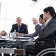 Stock Photo: Attractive businesswomin wheelchair during meting