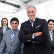 Senior manager with folded arms accompanied by his team — Stock Photo