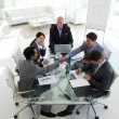 Businessmen shaking hands sitting around a conference table — Stock Photo