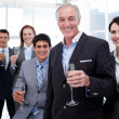 Smiling inernational business team holding glasses of Chamoagne — Stock Photo