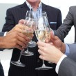 Close-up of business team toasting with Champagne - Stock Photo