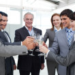 Cheerful business team toasting with Champagne - Stock Photo