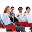 Business with thumbs up at a conference — Stock Photo