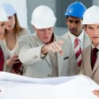 Multi-ethnic engineers studying plans — Stock Photo