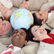 Smiling business lying around a globe — Stockfoto