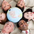 A diverse business lying on the floor around a globe — Stock Photo #10280875
